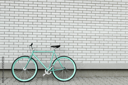 Fotobehang Fiets Teal bicycle next to white brick wall, copy space, no people