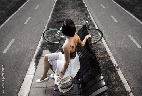 Artistic image, Young tattooed woman sitting on bench,next to bicycle and looking in distance Poster