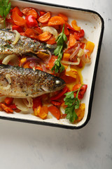 Fish with vegetables on baking tray