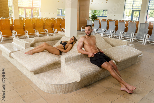 Beautiful young couple relaxing in spa center
