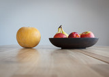 Round yellow melon and other fruits on a wooden table.