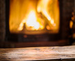 Old wooden table and fireplace with warm fire on the background. - 172657135