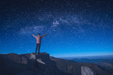 Man standing on a rocky cliff with raised hands - 172683524