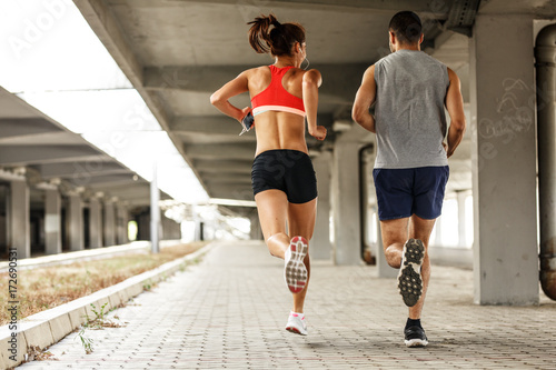 Couple of  runners jogging on the city street under the overpass.City environment.