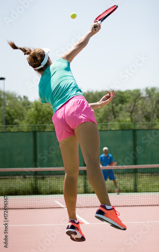 Fotobehang Tennis girl with a racket playing tennis on the court