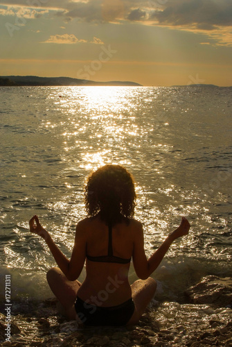 Young girl practicing yoga on seaside during the sunset