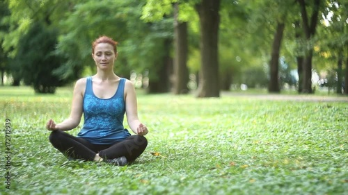 Poster Full of joy young women wearing sports clothes blue shirt and black tights in lotus position meditating in the quiet scenery of late summer in the park, camera is gently moving / Joy of doing yoga