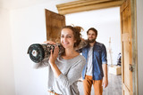 Young couple moving in new house, carrying a carpet. - 172715153