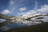 cielo riflesso nel lago di una montagna innevata - 172725531