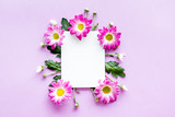 Floral mockup. Sheet of paper in frame of pink flowers on purple background top view