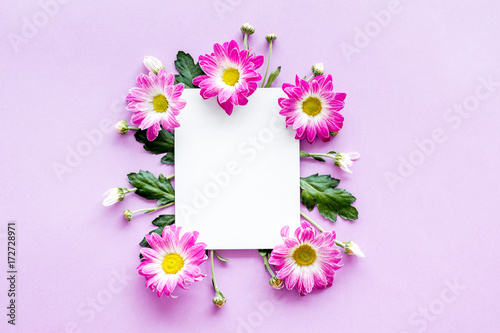 Floral mockup. Sheet of paper in frame of pink flowers on purple background top view - 172728971