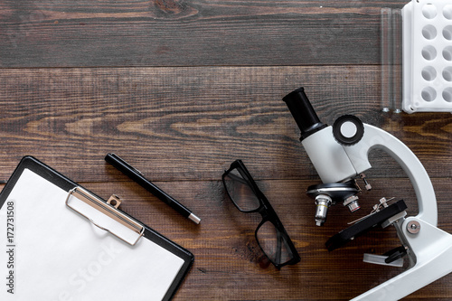 Microscope, pills and tablet on wooden background top view copyspace