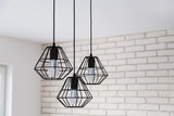 A modern loft chandelier made of black wire in a stylish white interior - 172737359