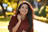Portrait of beautiful brunette woman in autumn red sweater. Cute girl walks in the autumn park - 172739777