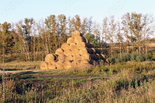 The pyramid is composed of hay balls in the rays of sunset.