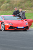 2 men standing nect to lamborghini race car on track