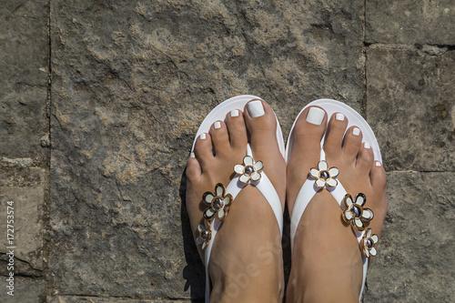 Foto op Aluminium Pedicure красивые женские ноги в пляжной обуви на каменной полу