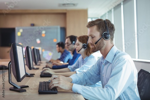 Businessman typing on keyboard at call center - 172755544