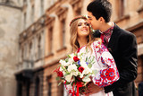 man kissing his girlfriend with blurred old european street on b - 172758398