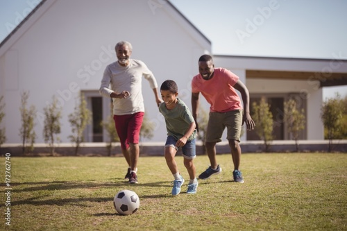 Fotobehang Voetbal Boy playing football with his father and grandson