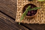 Marinated olives in bowl and rosemary herb on bamboo mat