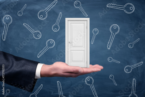 A small white door resting on a large businessman's palm with many keys drawn on a blackboard background Poster
