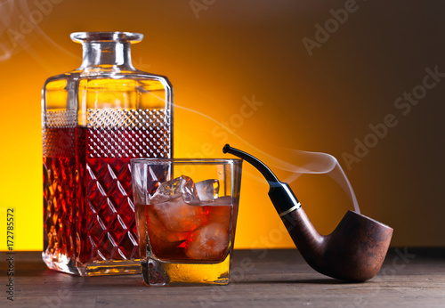 whiskey and pipe on a old wooden table,copy space for your text
