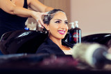 Beautiful young woman with hairdresser washing head at hair salon - 172786177