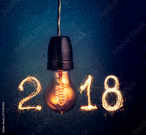 Foto Murales 2018 written with Sparkle firework and  light bulb , abstract 2018 Happy New Year background concept.