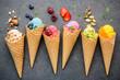 Leinwanddruck Bild - Various of ice cream flavor in cones blueberry ,strawberry ,pistachio ,almond ,orange and cherry setup on dark stone background . Summer and Sweet menu concept.