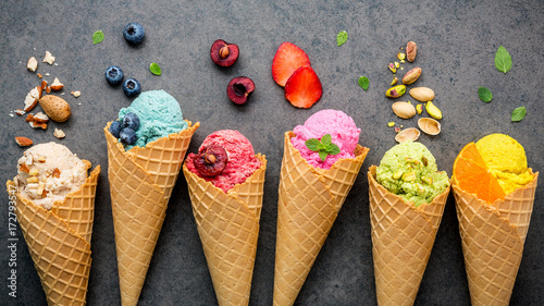 Leinwanddruck Bild Various of ice cream flavor in cones blueberry ,strawberry ,pistachio ,almond ,orange and cherry setup on dark stone background . Summer and Sweet menu concept.