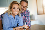 Portrait of mature couple standing in home kitchen - 172793941
