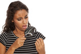 Upset young dark skinned woman looking her nails trough the magnifying glass - 172793969