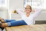 zufriedene frau sitzt zuhause und lehnt sich entspannt zurück - 172798924