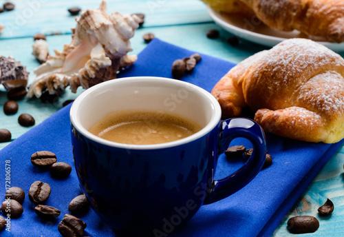 Staande foto Koffiebonen Caffè e brioche in blu, fuoco selettivo