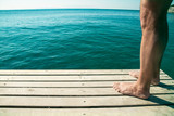 Male feet on the wooden pier over sea background