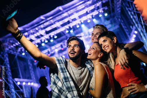 Happy friends taking selfie at music festival - 172811308