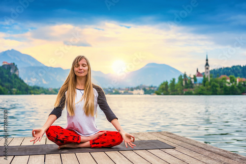 Fototapeta Woman doing yoga by the lake