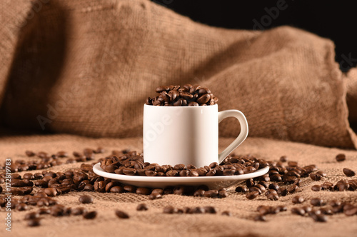 Fotobehang Koffiebonen White cup of coffee with brown aroma grain beans