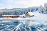 Blue ice and cracks on the surface of the ice. Frozen lake under a blue sky in the winter. Cabin in the mountains. Mysterious fog. Carpathians. Ukraine, Europe - 172825745