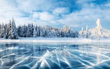Blue ice and cracks on the surface of the ice. Frozen lake under a blue sky in the winter. The hills of pines. Winter. Carpathian, Ukraine, Europe. - 172825764