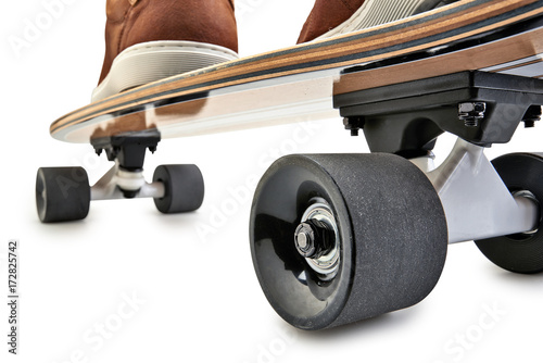 Fotobehang Skateboard Rear view of a Black and wooden skate board and brown leathers shoes
