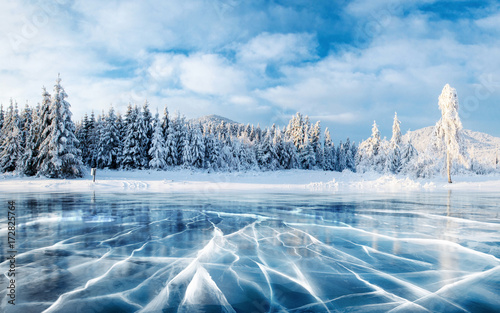 Blue ice and cracks on the surface of the ice. Frozen lake under a blue sky in the winter. The hills of pines. Winter. Carpathian, Ukraine, Europe. © standret