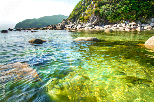 Foto op Canvas Mediterraans Europa beautiful beach lots of high stones from the destroyed rocks, trees grow.