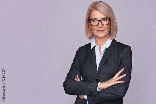 Poster Smile senior business woman with folded hands