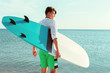 Handsome surfer holding his surfboard