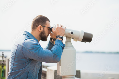 Trendy male person look in binocular telescope