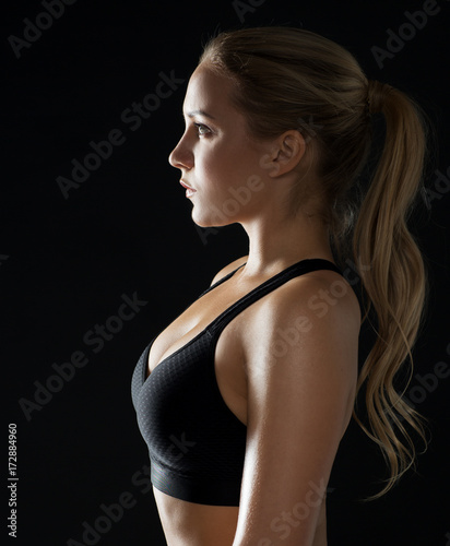 Wall mural young woman in black sportswear posing in gym