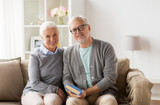 happy senior couple sitting on sofa at home - 172887545