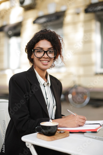 Portrait of African American girl in glasses sitting at the table of cafe and happily looking in camera with pen in hand. Lady with dark curly hair working with cup of coffee and laptop on table